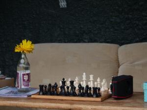 Ein Biertisch, in der Mitte ist ein aufgebautes Schachbrett, danaben eine leere Flasche mit einer Blume drin.