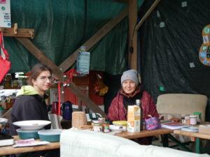 Zwei Aktivist:innen sitzen an einer Bierbank und lächeln in die Kamera